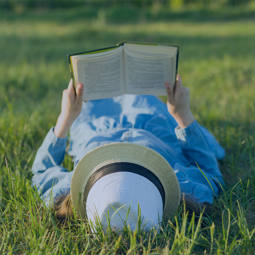 someone laying down in the grass reading a book