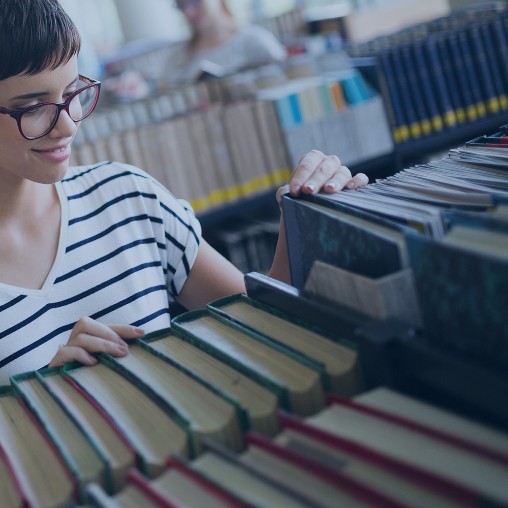 person selecting a book from a shelf of books